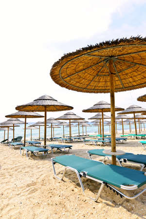 Straw umbrellas on empty seaside beach in Greece