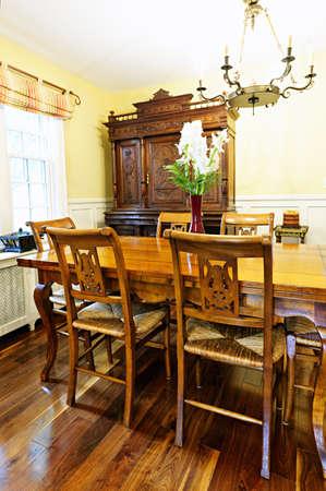 arredamento classico: Sala da pranzo interna con antico tavolo di legno e sedie in casa