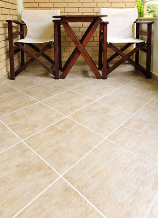 Wooden chairs and table on ceramic tile floor of balcony Archivio Fotografico