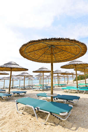 Umbrellas and lounge chairs on empty seaside beach in Greece photo