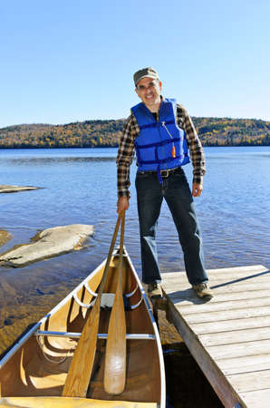 Man standing on dock with canoe on Lake of Two Rivers, Ontario, Canada photo
