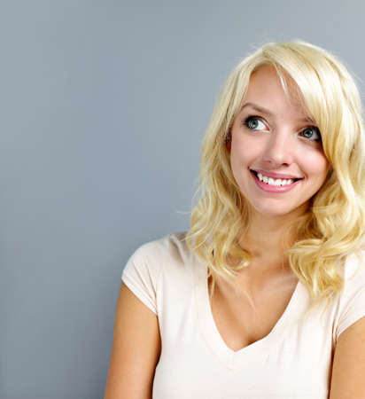 congenial: Smiling blonde caucasian woman looking up on grey background