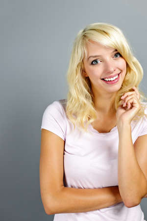 Portrait of smiling young blonde caucasian woman on grey background Stock Photo - 11106485