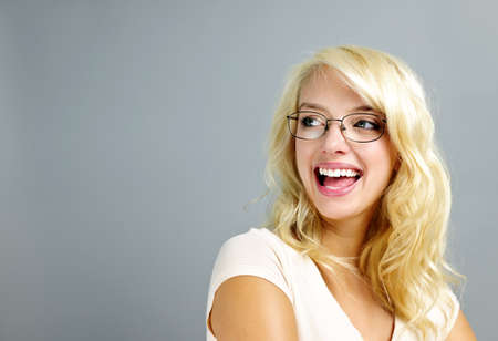 Happy young woman wearing eyeglasses looking to the side on grey background photo