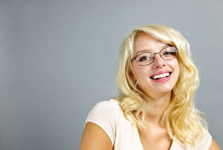 Smiling young woman wearing eyeglasses on grey background photo