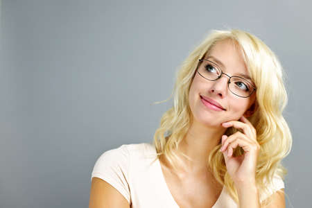Thoughtful young woman wearing eyeglasses on grey background looking up photo