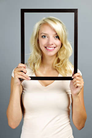 Portrait of smiling young woman holding picture frame on grey background photo