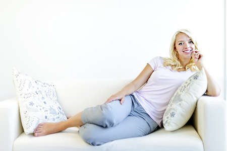 Mooie blonde vrouw op de bank ontspannen met de voeten omhoog in huis