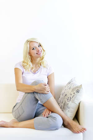 Pretty blonde woman sitting on couch at home and smiling