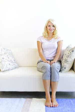 Pretty blonde woman sitting on sofa at home smiling