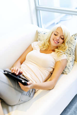 woman on couch: Happy blonde young woman laying on couch with tablet computer at home