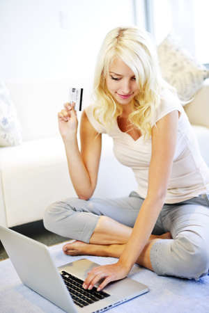 surf shop: Happy blonde woman internet shopping online at home Stock Photo