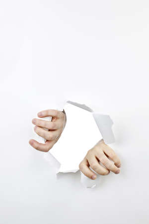 Hands ripping a hole in white paper with torn edges photo