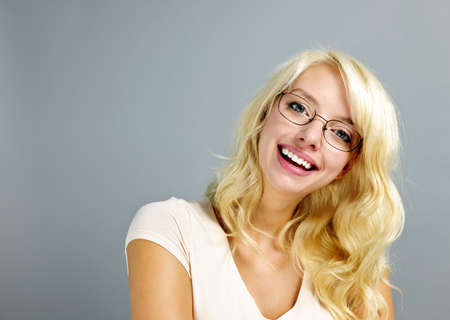 Happy young woman wearing eyeglasses on grey background Stock Photo - 11372117