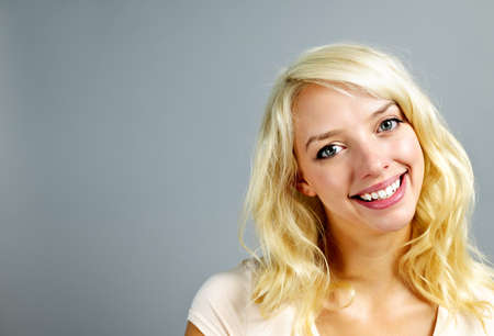 Portrait of smiling young blonde caucasian woman on grey background Stock Photo - 11372118