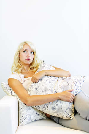 Thoughtful beautiful blonde woman hugging cushion on couch photo