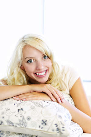 Portrait of smiling blonde woman relaxing on couch in living room at home photo