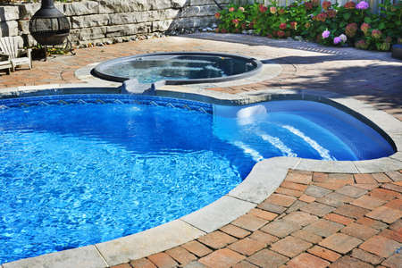 Outdoor inground residential swimming pool in backyard with hot tub Stock Photo
