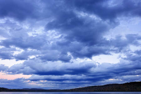 Blue cloudy dramatic sky at sunset over forest wilderness in Algonquin Park, Canada photo