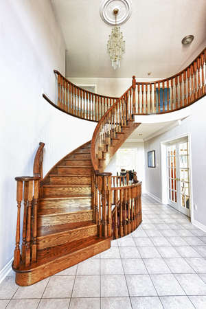 Curved oak staircase in luxury home entrance hall photo