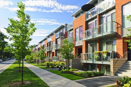 Case di città moderna di mattoni e vetro su strada urbana