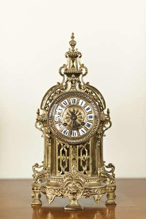 Antique bronze shelf clock with ornate decoration photo