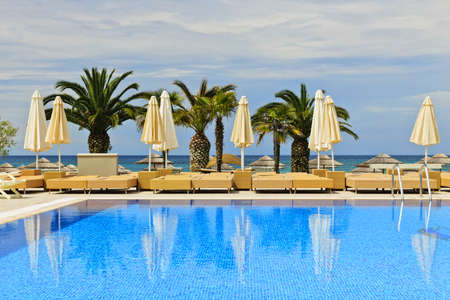 pool deck: Idyllic swimming pool at tropical resort with palm trees in Greece