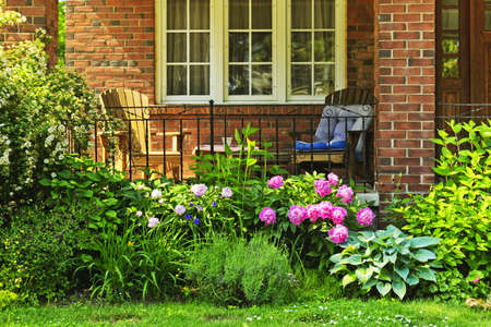 Front of home with chairs and flower garden photo