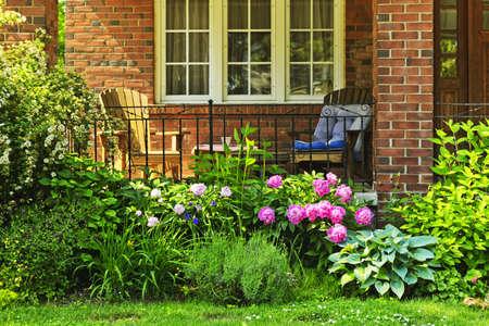 Voorkant van huis met stoelen en bloementuin Stockfoto
