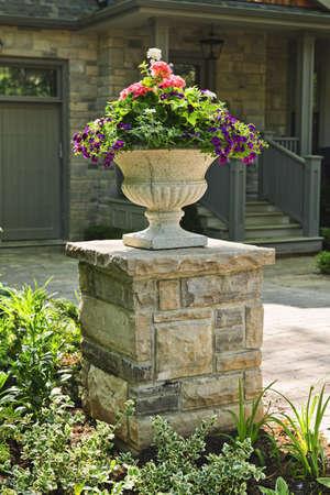 jardineras: Piedra maceta con flores cerca de entrada de la casa