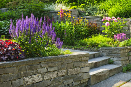 wall decor: Natural stone landscaping in home garden with steps and flowerbeds Stock Photo