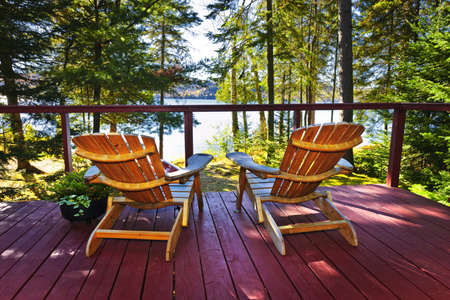 deck: Wooden deck at forest cottage with Adirondack chairs