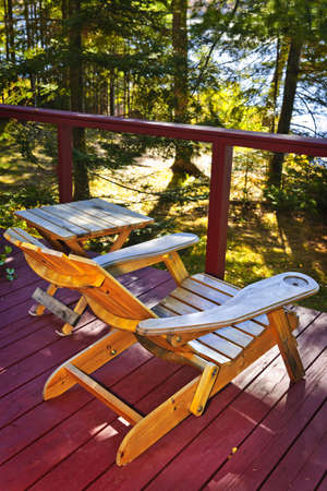 Wooden deck of cottage with lake view and Adirondack chair photo