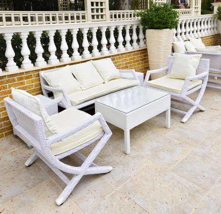 furniture: Wicker patio furniture outdoor in area paved with natural stone