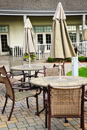 patio furniture: Mobilia del patio con tavoli sedie e ombrelloni