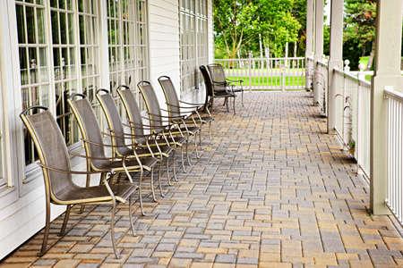 empedrado: Hilera de sillas de metal en el patio de ladrillos contra las ventanas Foto de archivo