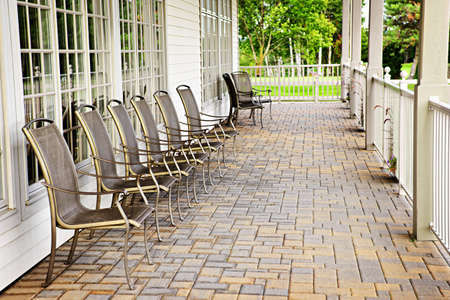 Row of metal chairs on brick patio against windows photo