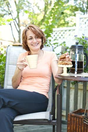 Gelukkige vrouw ontspannen met koffie en koekjes op ligstoel in de achtertuin thuis