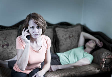 Concerned woman with sick senior mother calling emergency photo