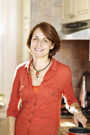自宅のキッチンで料理を楽しむ笑顔の成熟した女性 写真素材