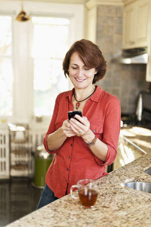 Smiling mature woman texting on phone in kitchen at home