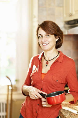 Smiling mature woman enjoying cooking in kitchen at home photo