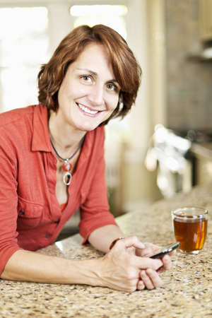 Smiling mature woman texting on phone in kitchen at home Stock Photo - 12389854
