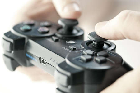 gaming: Male hands holding video game controller closeup