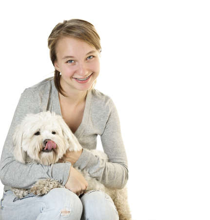 Pretty teenage girl holding adorable coton de tulear dog photo
