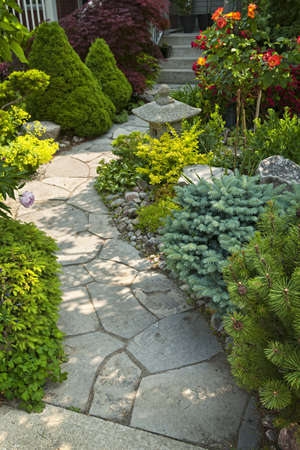 backyards: Natural flagstone path landscaping in home garden Stock Photo