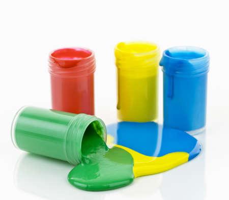 Open containers van verf in primaire kleuren gemorst en gemengd