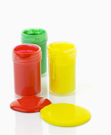 dripping paint: Open containers of paint in primary colors spilled and mixed