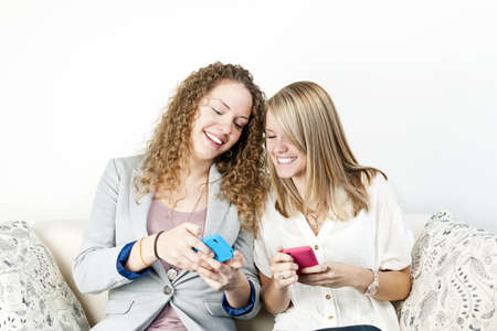 Two smiling women using mobile devices with colorful cases photo