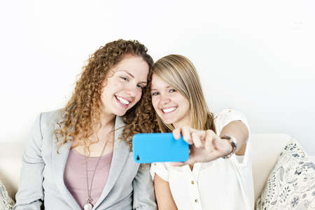 Two smiling women using cellular mobile phone to take a picture photo